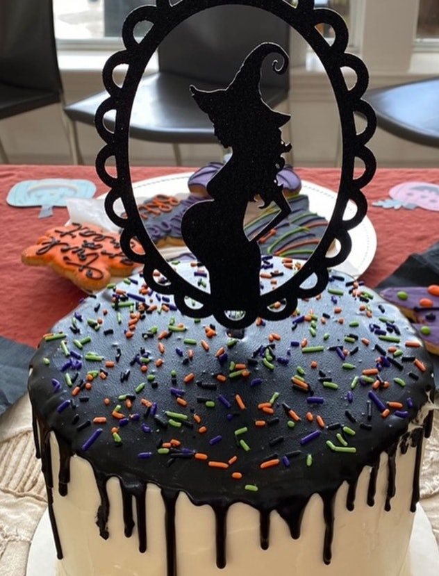 White cake with black dripping icing, orange and green sprinkles, and a cake topper of a pregnant wi...