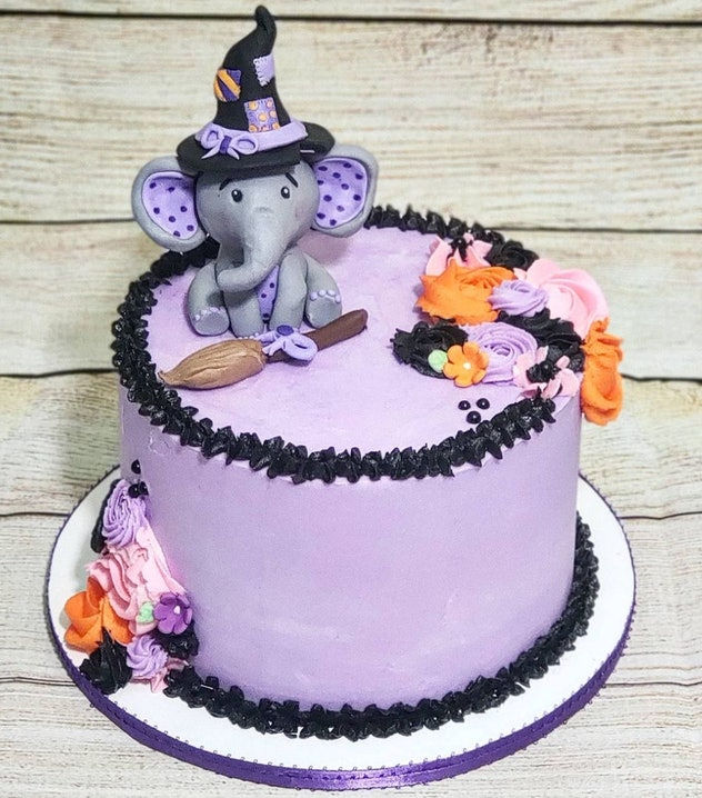 Purple and black cake with baby elephant wearing a witch's hat
