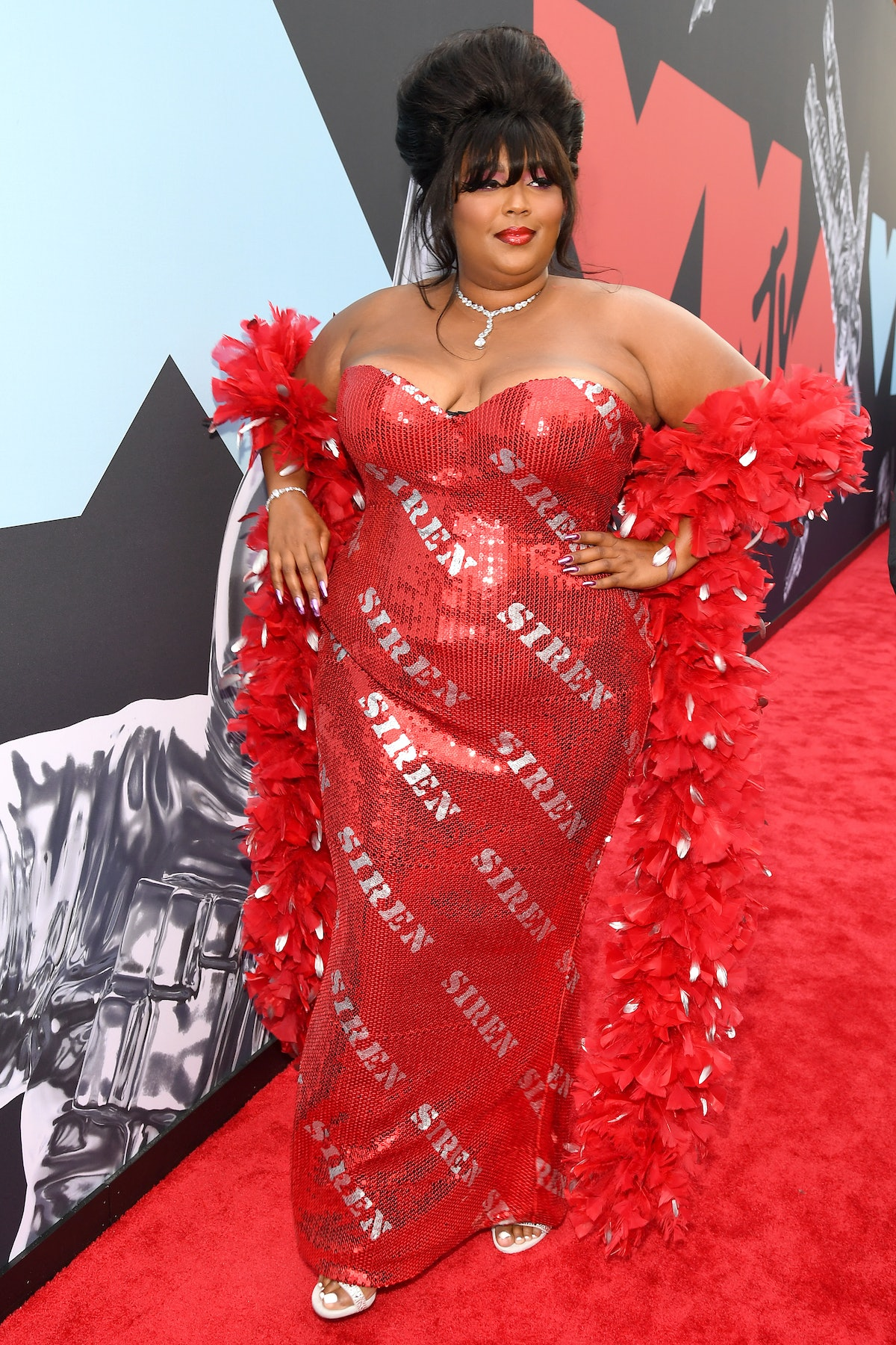 """Lizzo in red gown with the words """"Siren"""" on it."""