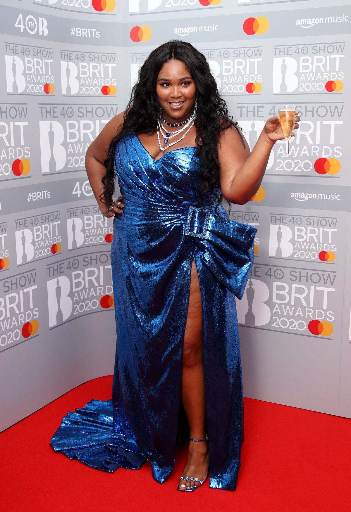 Lizzo with champagne in blue gown.