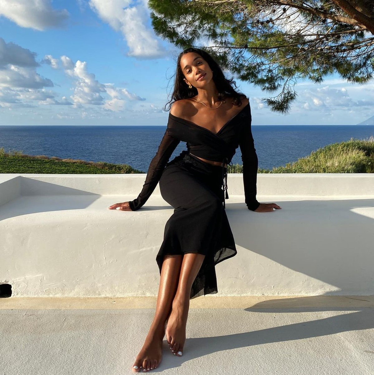 Actor Laura Harrier wears black two-piece top and skirt set on Instagram.