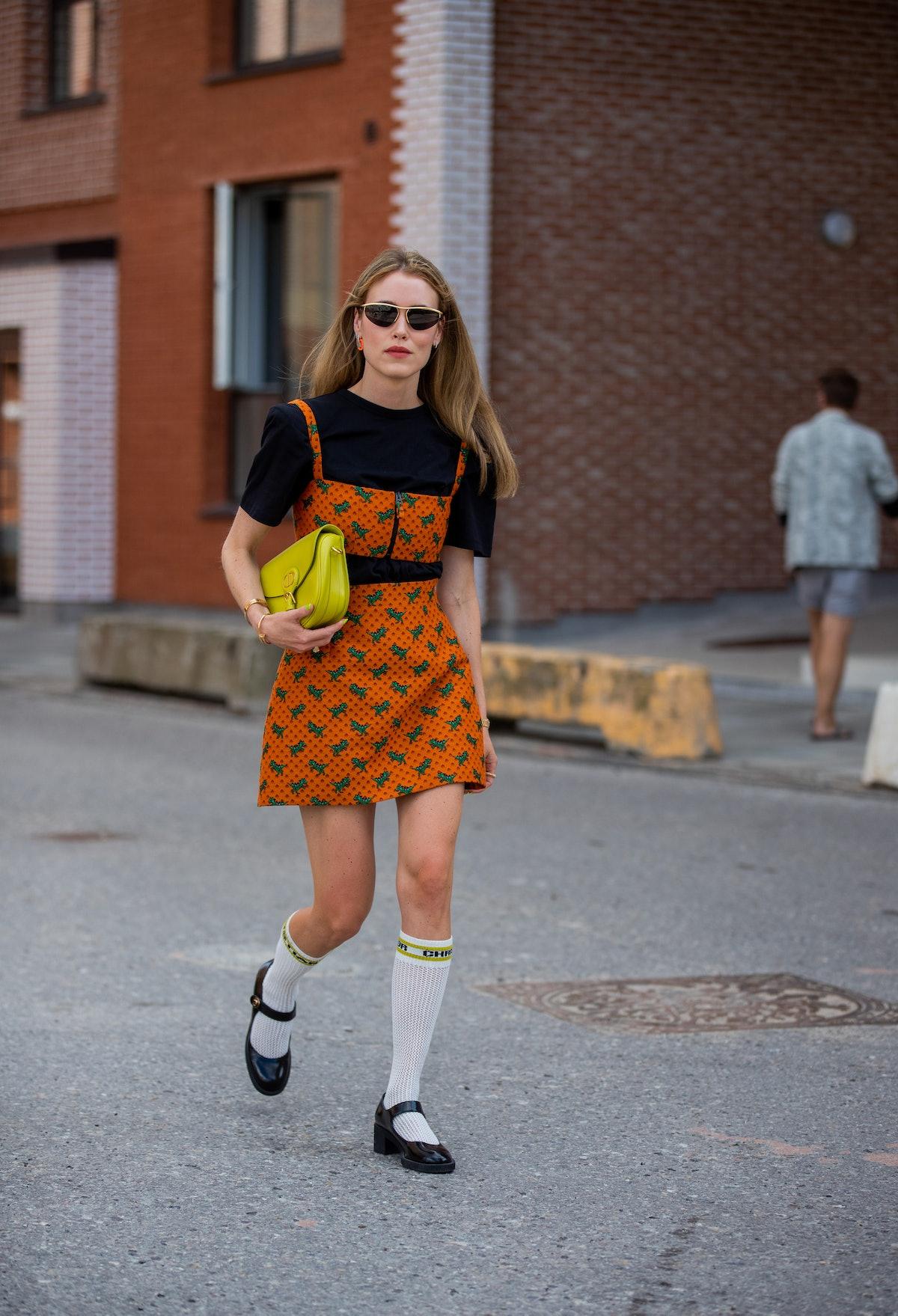 Annabel Rosendahl seen wearing orange dress with print, neon bag, knee socks and shoes outside Desig...