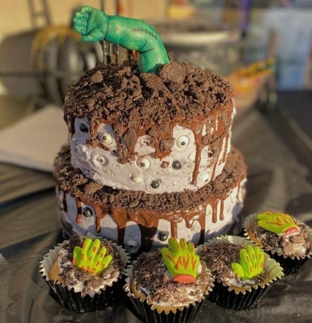Two layer cake with baby arm decorated to look like a zombie/monster coming out like it's coming out...