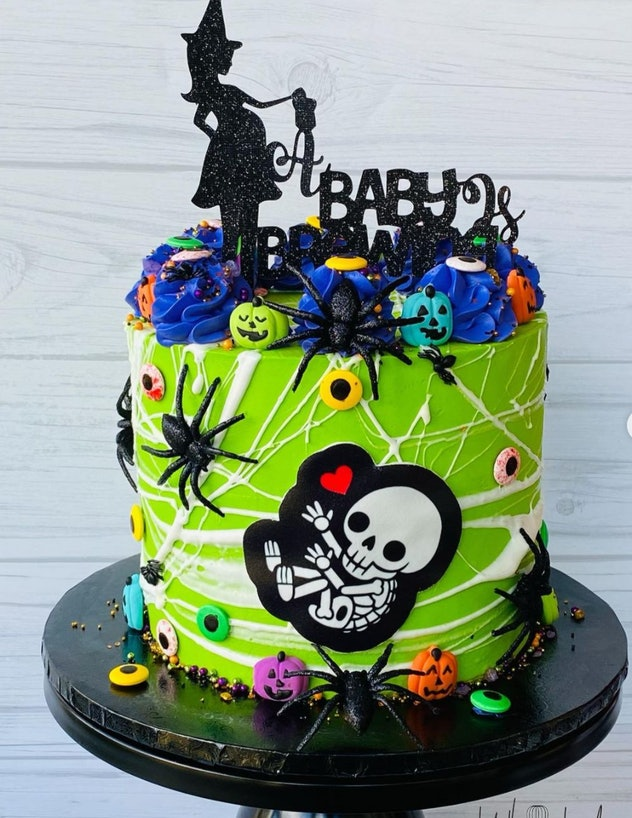 Green cake with Halloween details, spider webs, and a pregnant witch cake topper