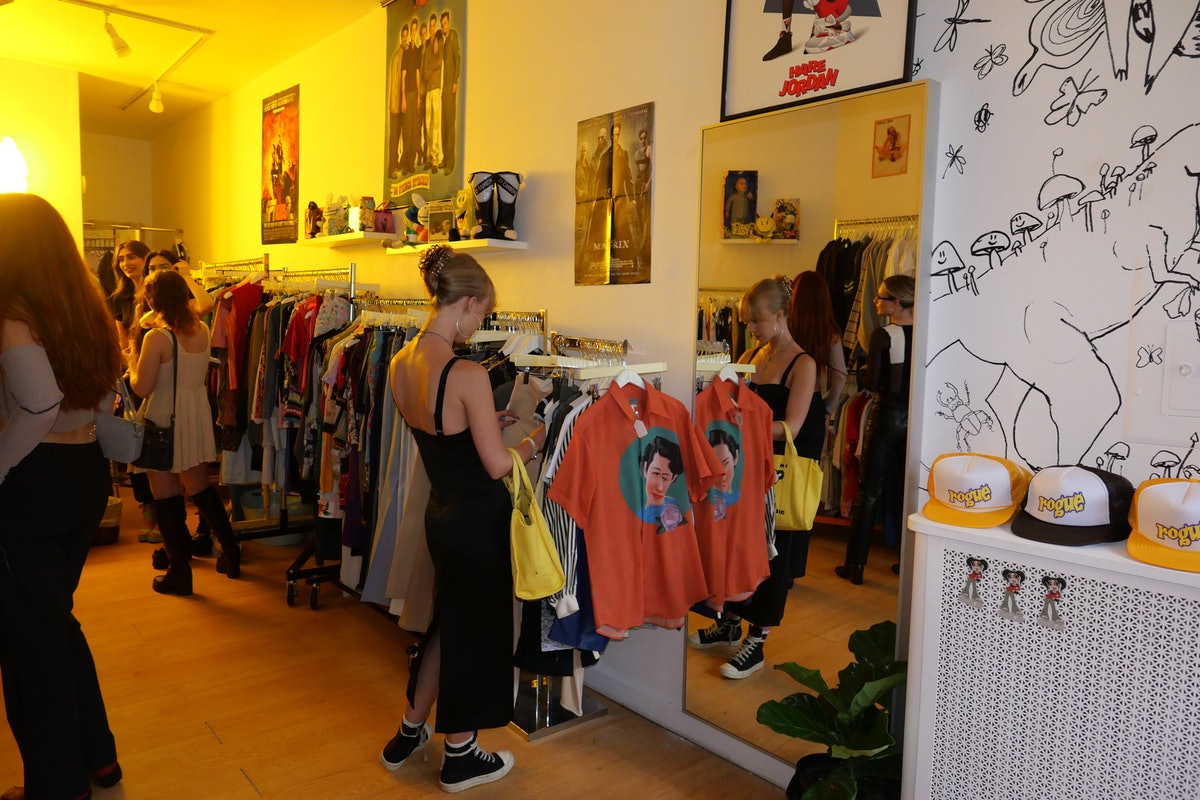 A blonde woman in a long black dress and sneakers browses racks of vintage clothing at Rogue in New ...