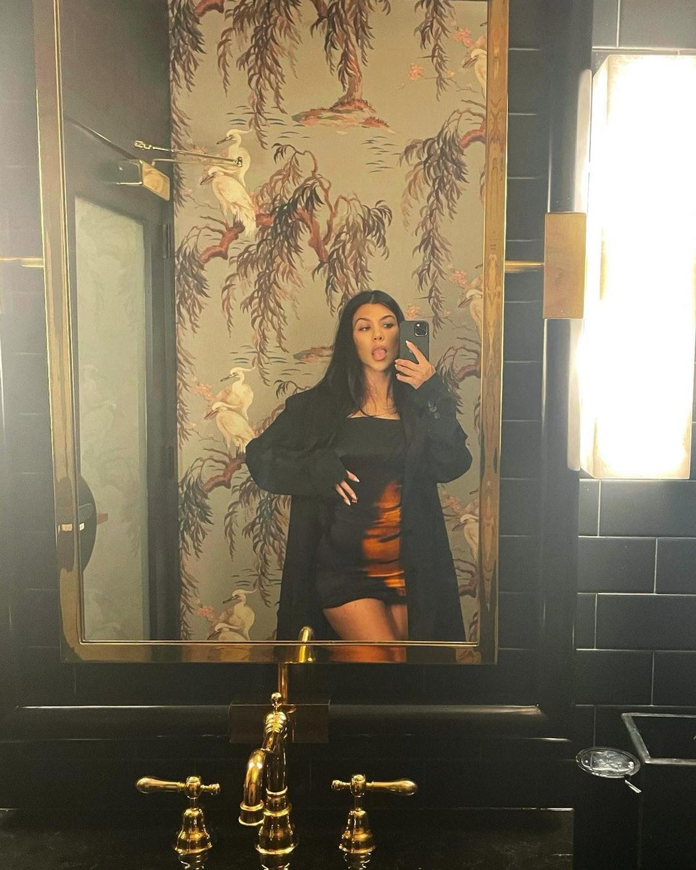 Kourtney Kardashian wears silky slip dress from MSBHV while posing for a mirror selfie on Instagram.