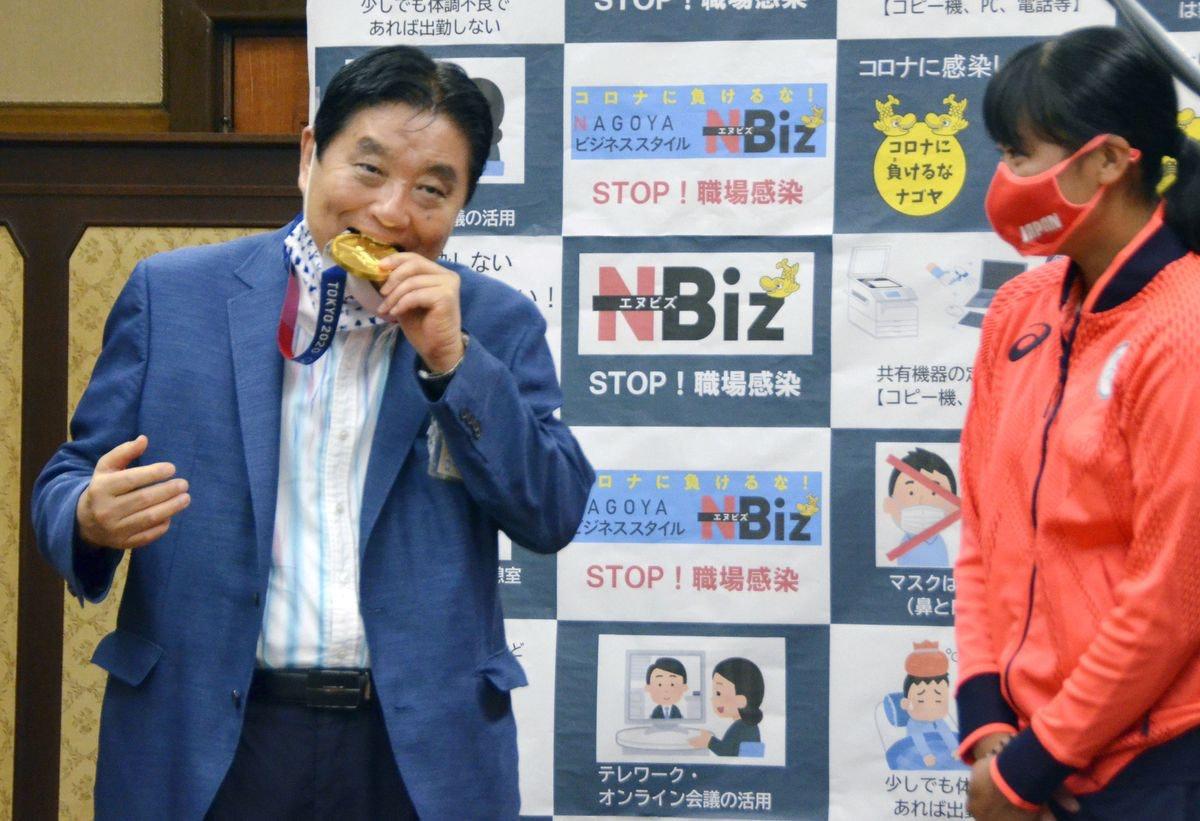 Nagoya mayor Takashi Kawamura bites into an Olympic gold medal belonging to softball player Miu Goto...