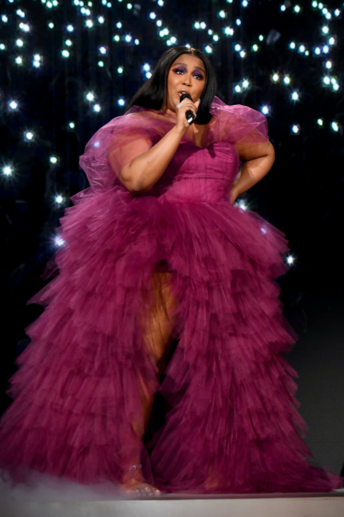 Lizzo performing in a burgundy gown.