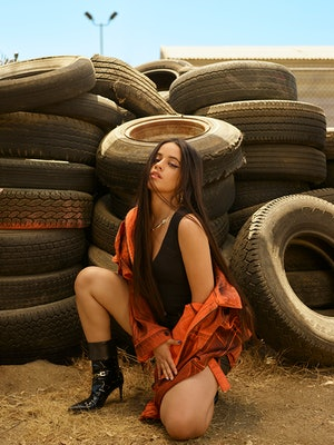 Camila Cabello poses against a stack of tires wearing a Calvin Klein Jeans top, Levi's Premium short...