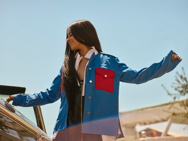 Bustle cover star Camila Cabello stands outside wearing a blue and red jacket by Louis Vuitton.