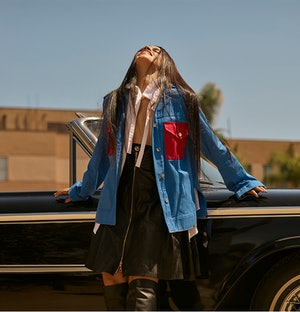 Bustle cover star Camila Cabello poses against a vintage car wearing a blue and red Louis Vuitton ja...