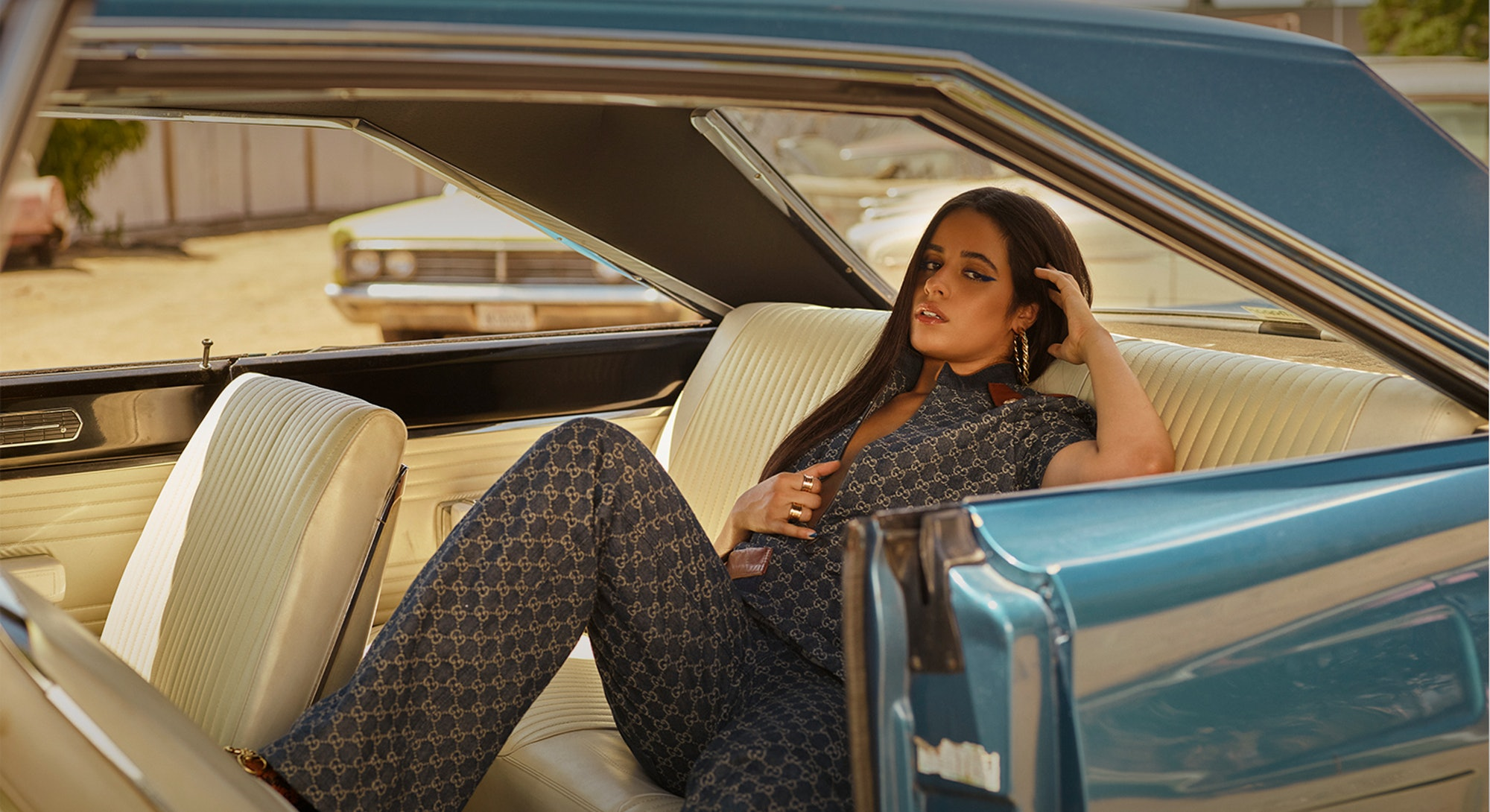 Camila Cabello wears denim Gucci while posing in a car for the cover of Bustle's denim issue.