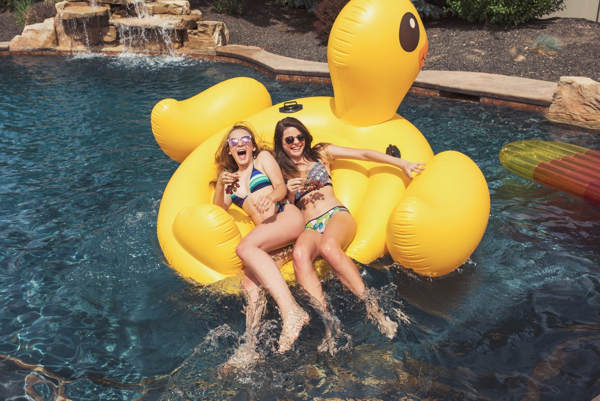 2 friends on a duck raft in a pool before heading to the beach with summer captions with friends.