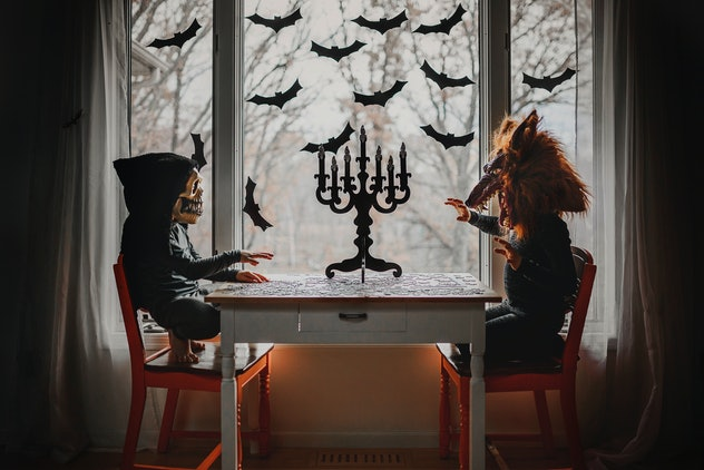 Two kids wearing Halloween masks, sitting at a table with a candelabra, in front of a window with ba...