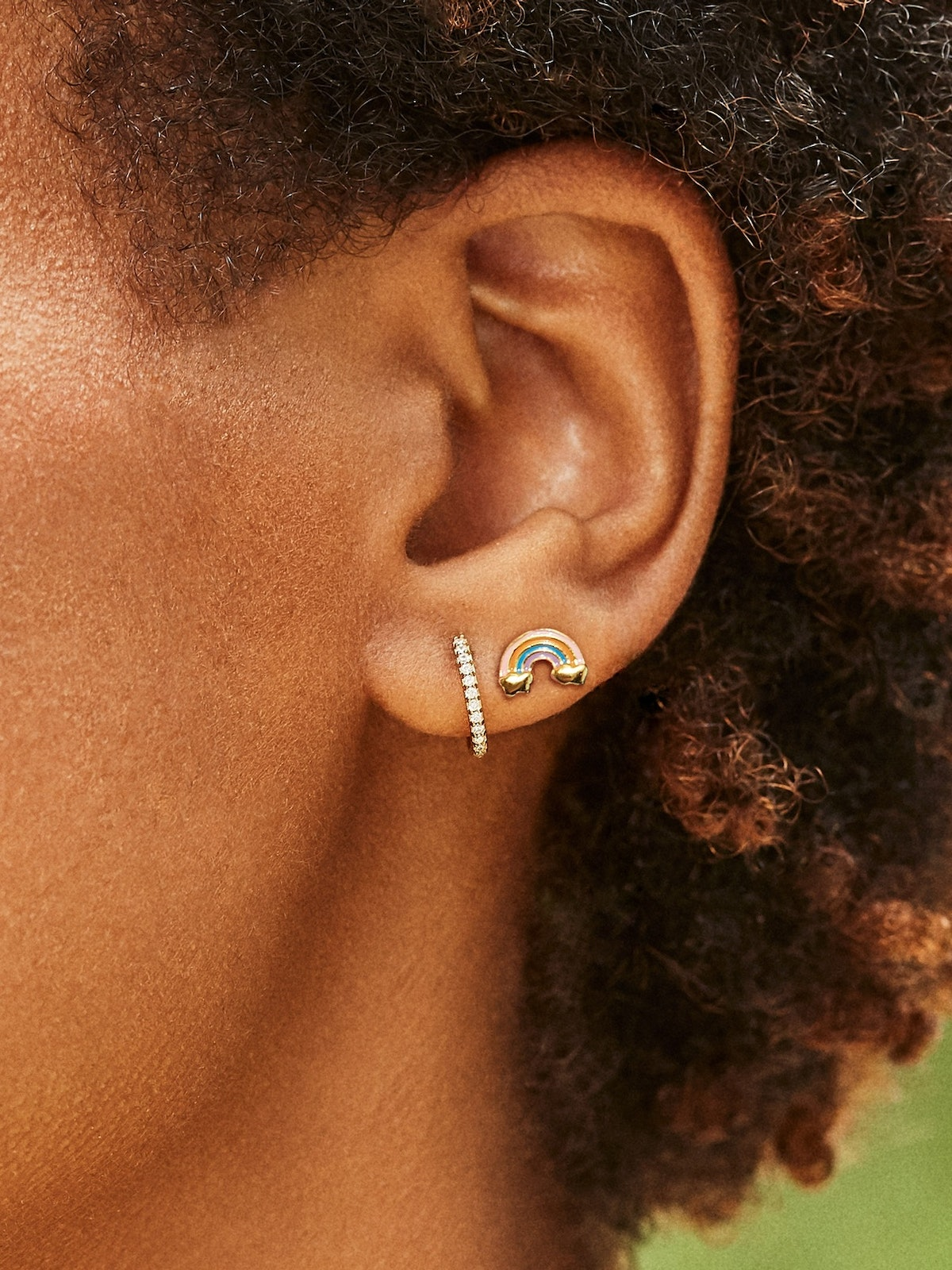 A black model with short, natural hair texture models two dainty pieces of jewelry: a rhinestone hoo...