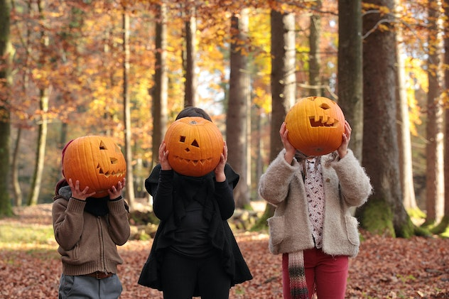 Three kids standing in a row in wooded area, holding Jack-o-lanterns over their faces