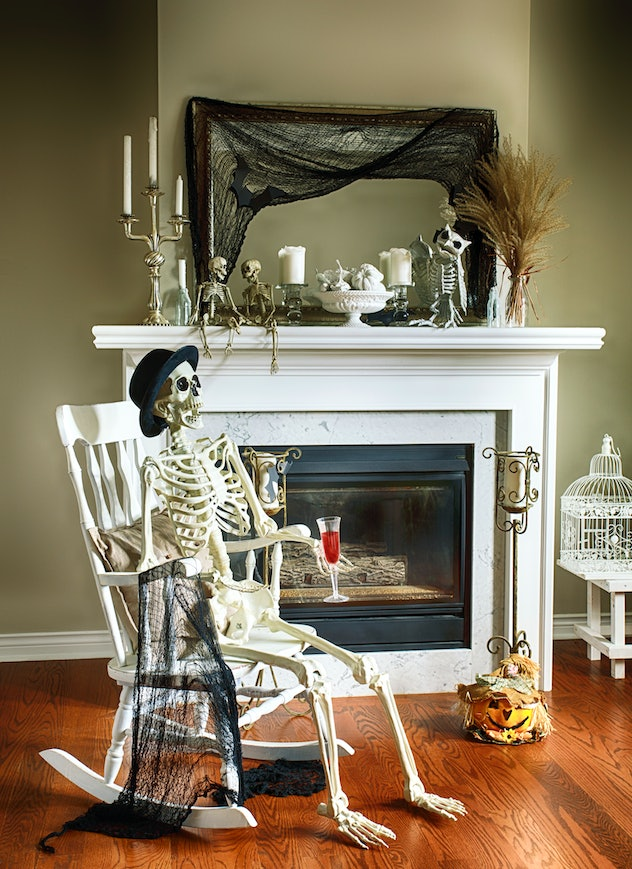 A fireplace decorated in spooky Halloween decor with a skeleton siting in a rocking chair in front o...