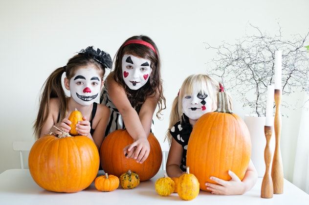 Three girls sitting at table with pumpkins, their faces painted like clowns in black, white, and red...