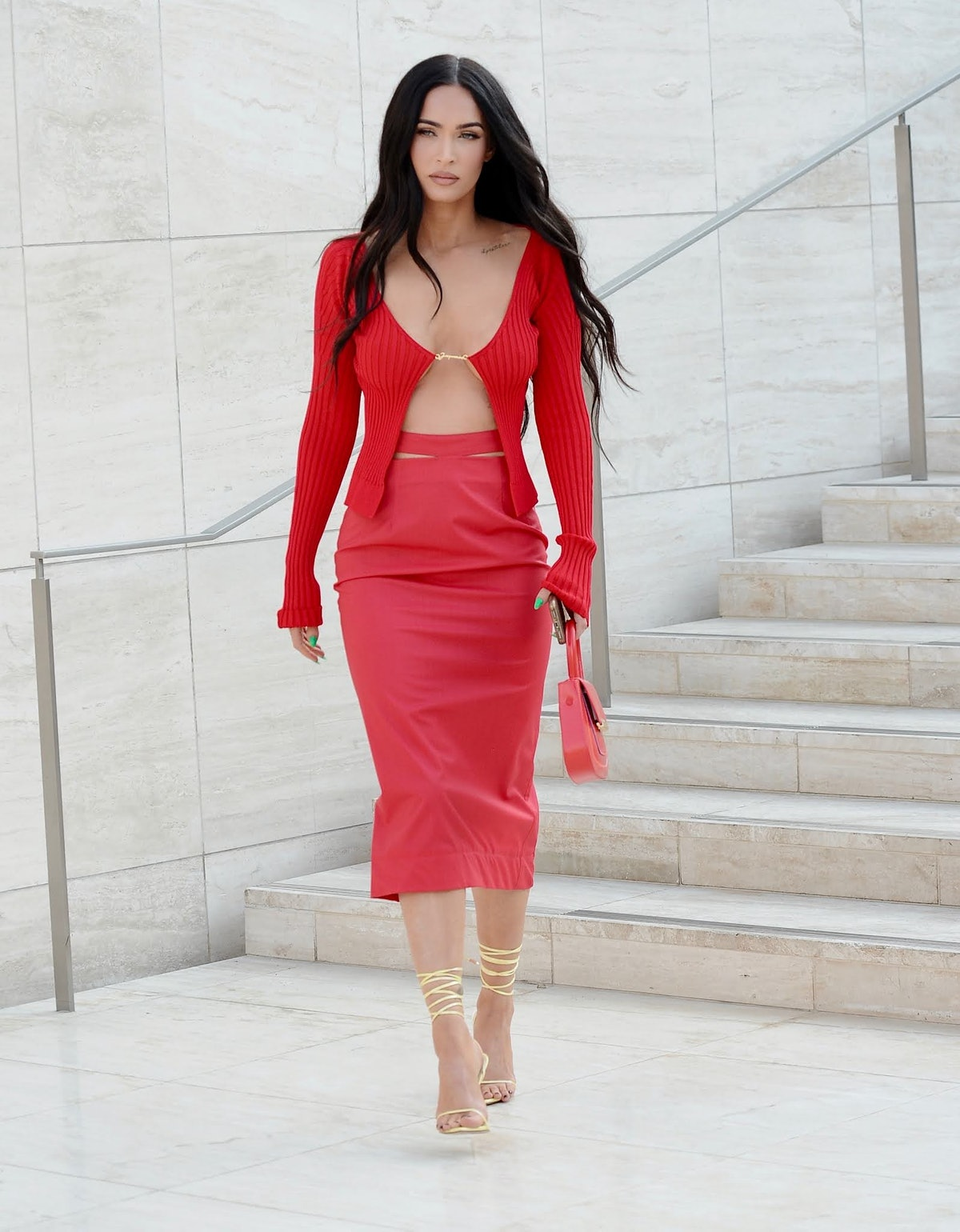 Megan Fox wears Jacquemus cardigan with a red skirt and gold strappy heels.