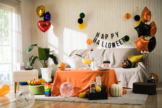 A couch with Halloween decor all around it, and a coffee table with orange drape sitting in front.