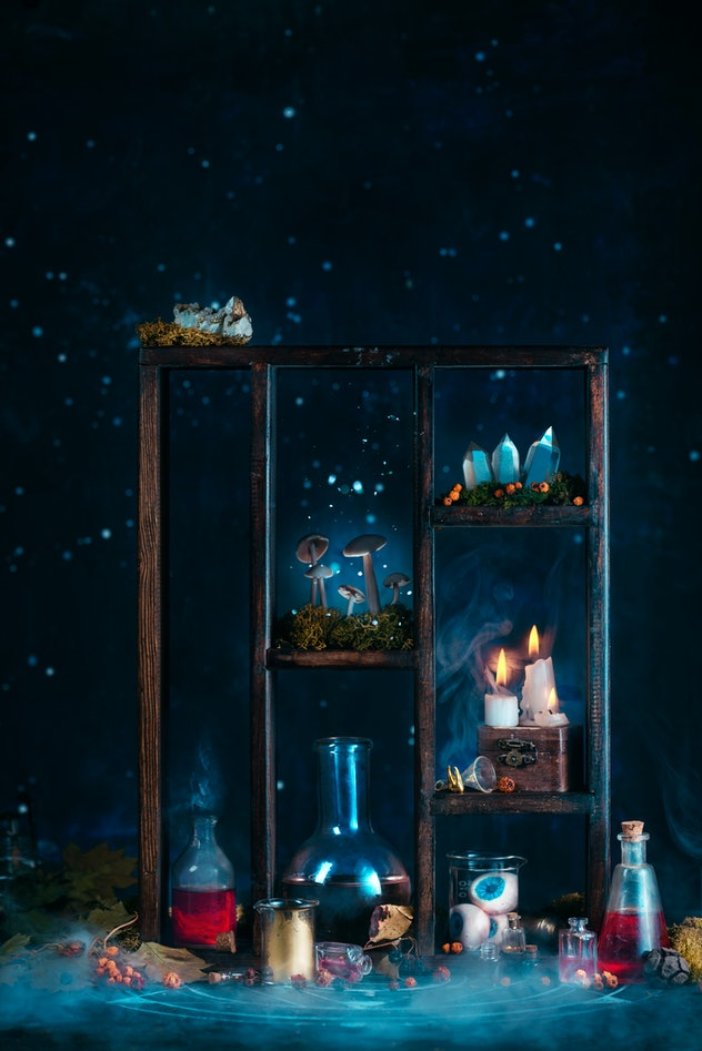 Shelving with beakers filled with colorful liquids, lit candles, and spooky Halloween decor