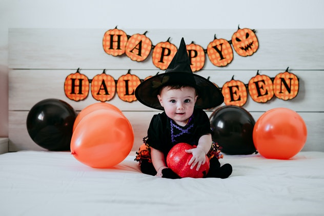 """Baby dressed up in witch costume, sitting on bed with black and orange balloons on either side and """"..."""