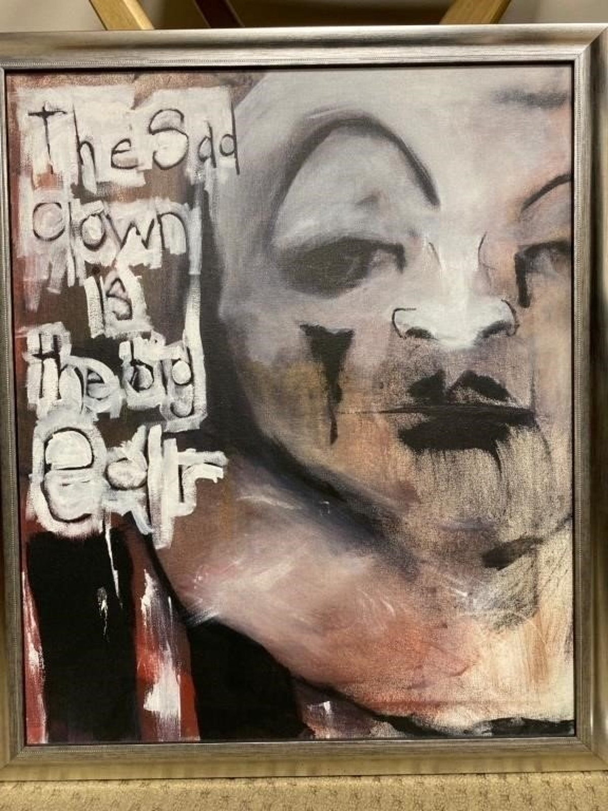 Framed artwork of a sad clown.