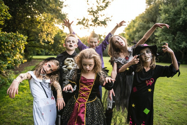Several kids dressed as zombies, posing for camera