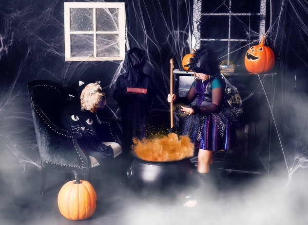 Little girl dressed up as a witch, stirring a pretend cauldron in haunted house