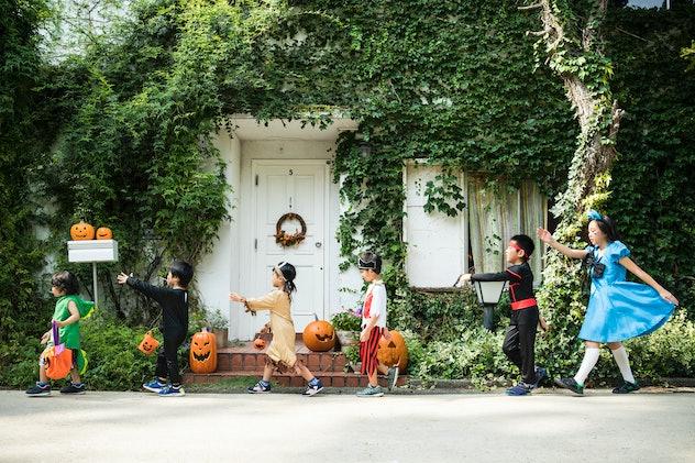 Wide shot of six kids walking in a line, dressed in Halloween costumes