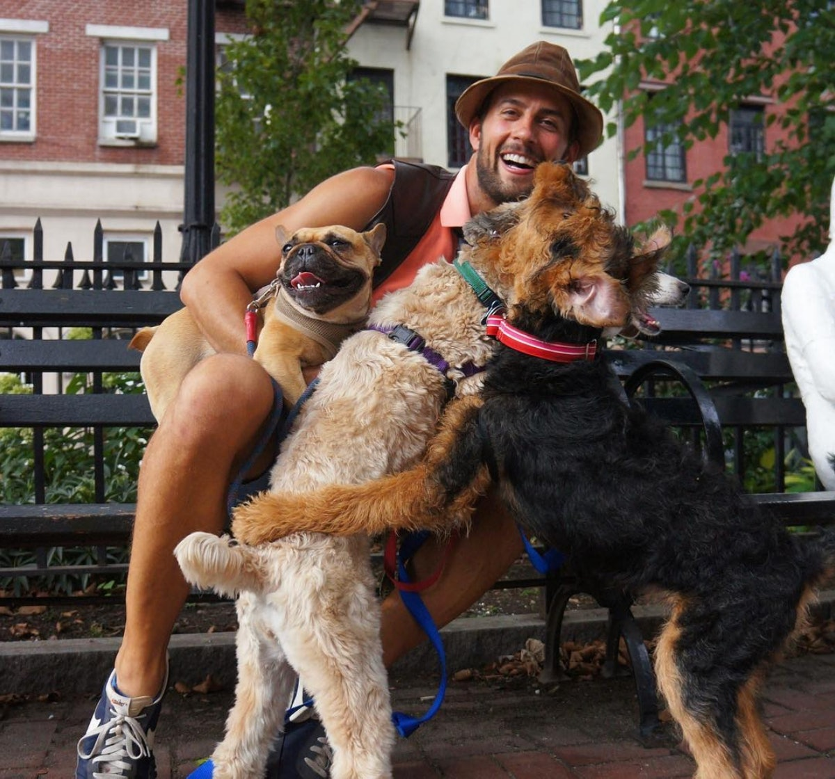 Ryan Fischer smiling and sitting on a bench with a bunch of happy dogs.