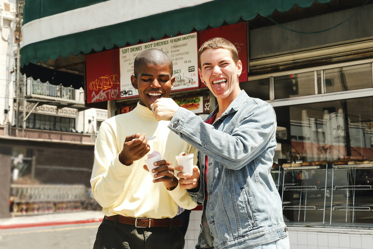 Two young males being playful while eating ice cream in front of a cafe during the day, waiting to p...