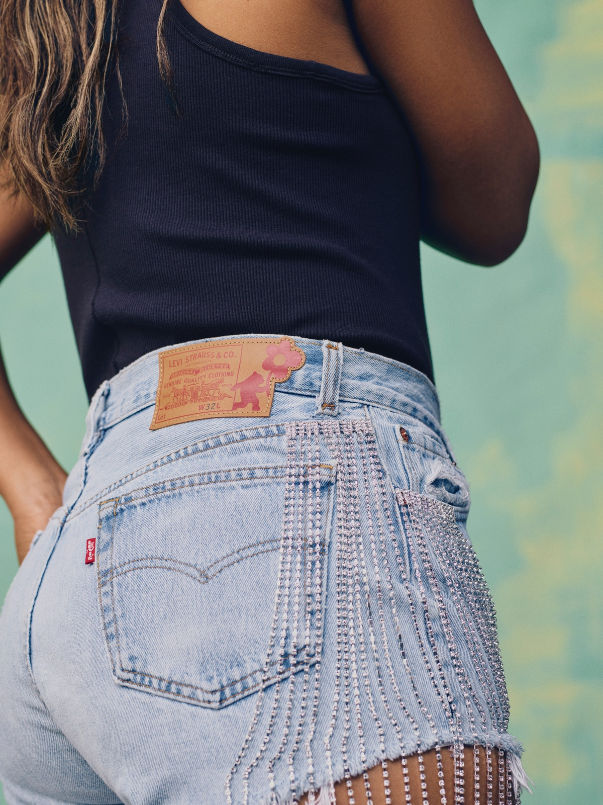 Tennis star Naomi Osaka wears crystal-embellished short denim shorts in the campaign for her Levi's ...