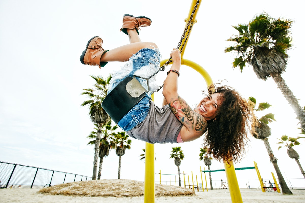 Young woman smiling and swinging at the park before posting swing quotes for Instagram captions.
