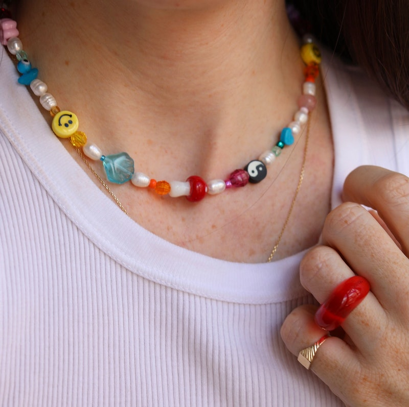 A woman wears a beaded necklace. Mindful beading is one activity in art therapy for anxiety.