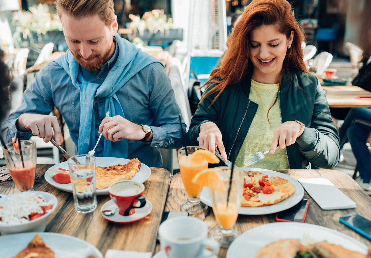 Young couple having omelettes and waffles before posting a pic on Instagram with brunch quotes, capt...