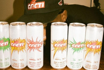 Travis Scott posing behind rows of Cacti spiked seltzer