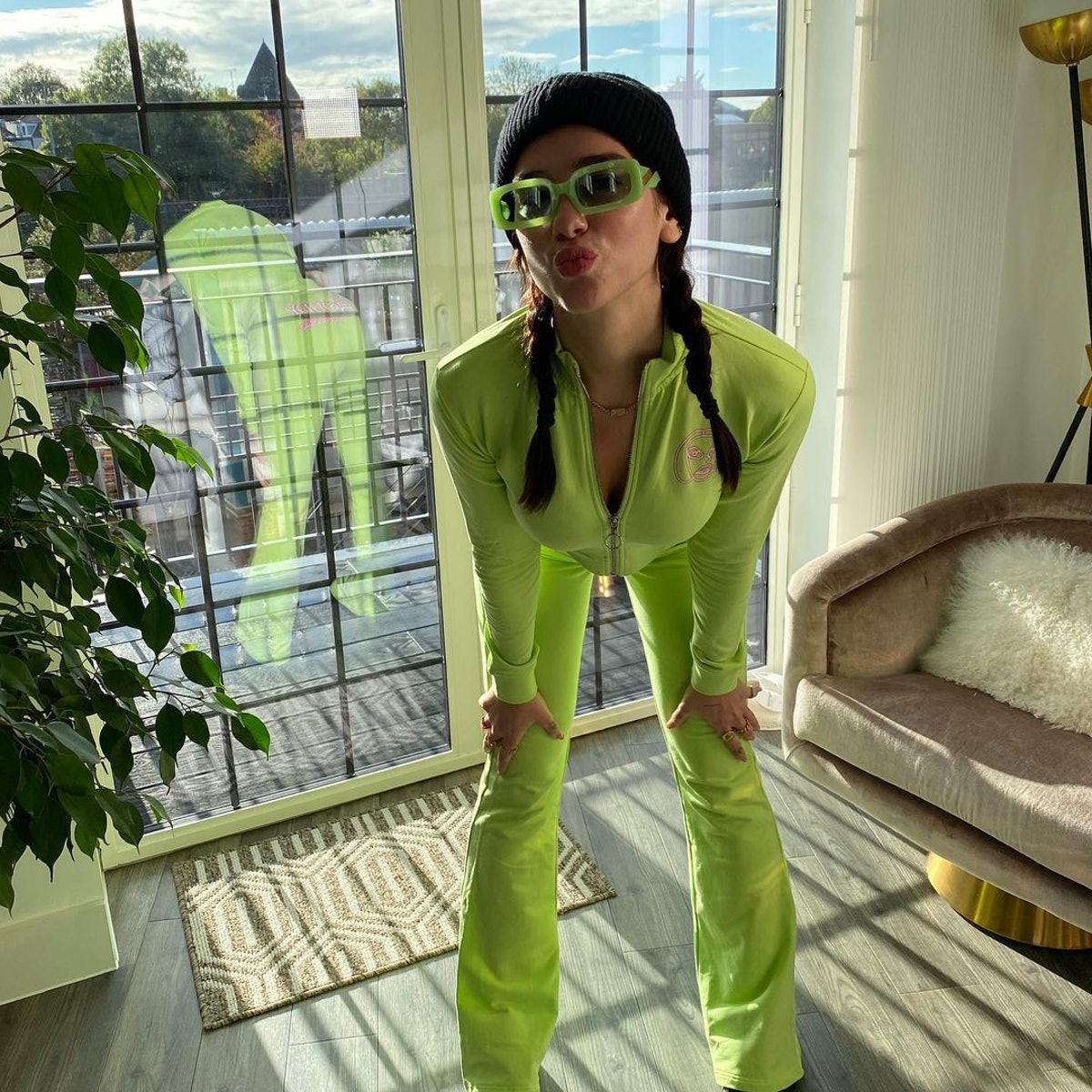 Dua Lipa wears a neon orange tracksuit adorned with '90s-style braided pigtails.