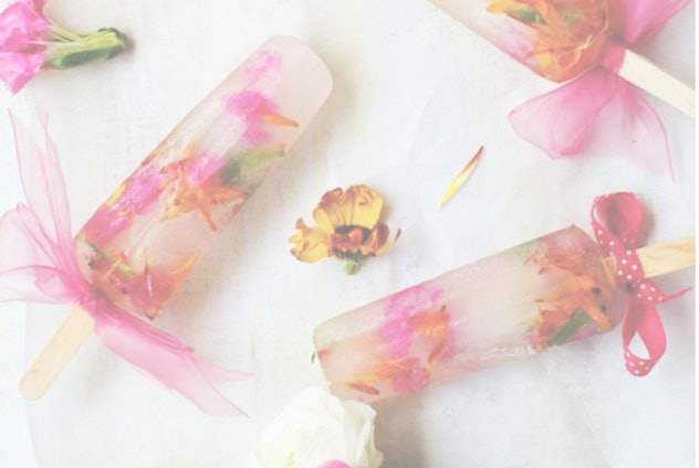 Image from the website studiodiy.com of clear popsicles with edible flowers.