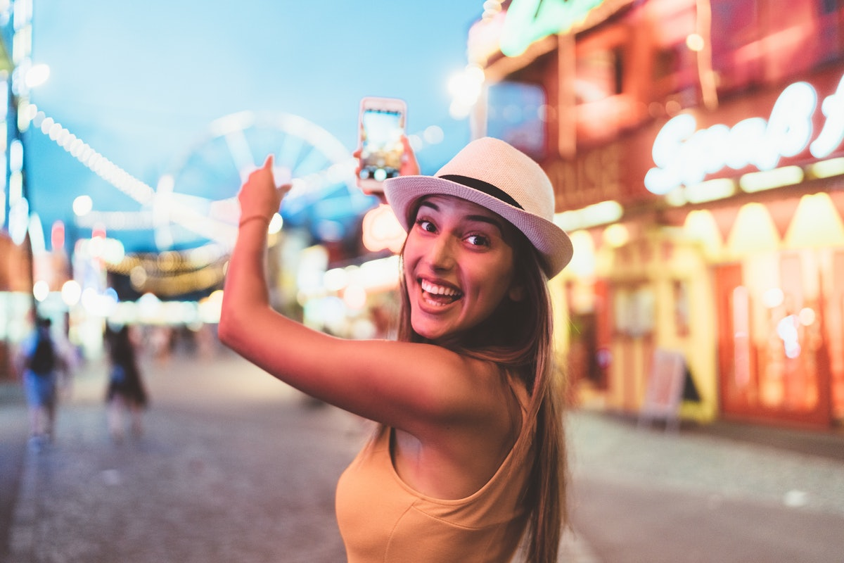 Young woman pointing to a Ferris wheel at an amusement park before posting a Ferris wheel quote on I...