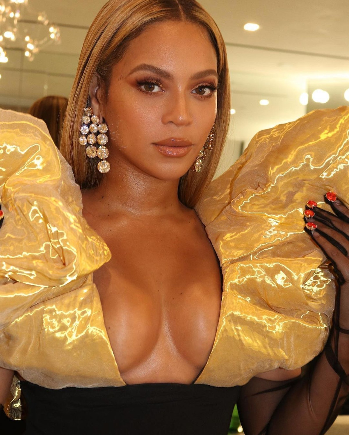 Beyoncé in gold dress and gloves selfie