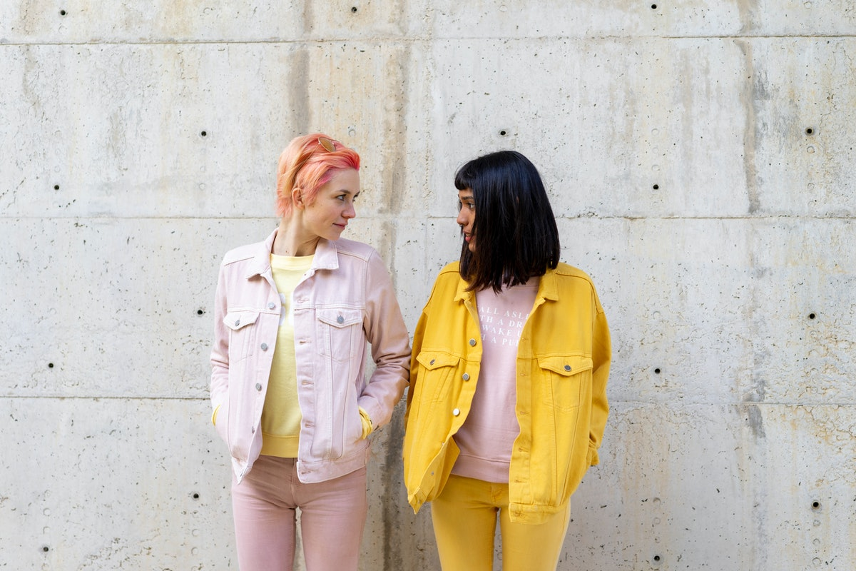 2 friends leaning against a wall looking at each other before posting on Instagram with a caption fo...