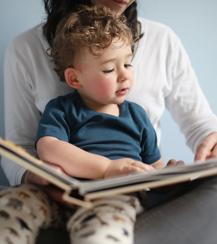 toddler sitting on mom's lap, reading a children's book