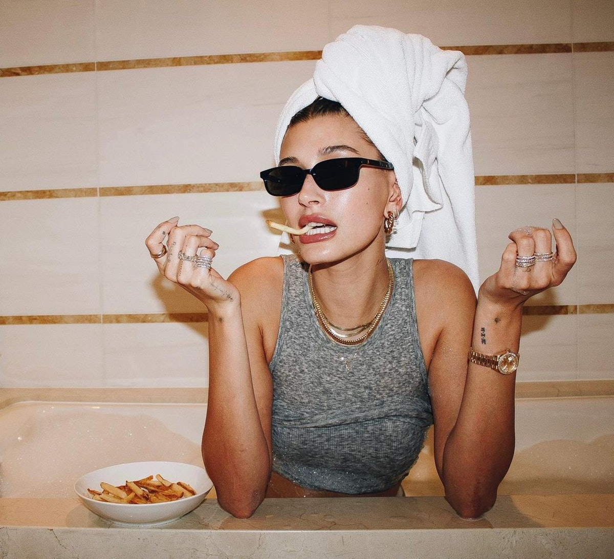 Hailey Bieber eating fries in towel and sunglasses