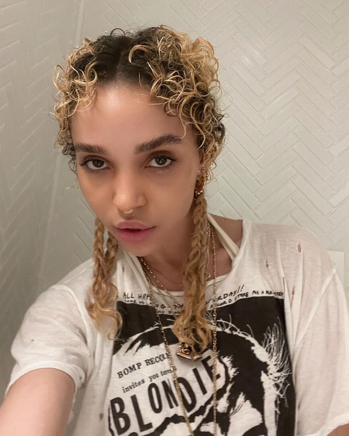 FKA Twigs wearing the braided pigtail style, a nostalgic look that's back and on-trend.
