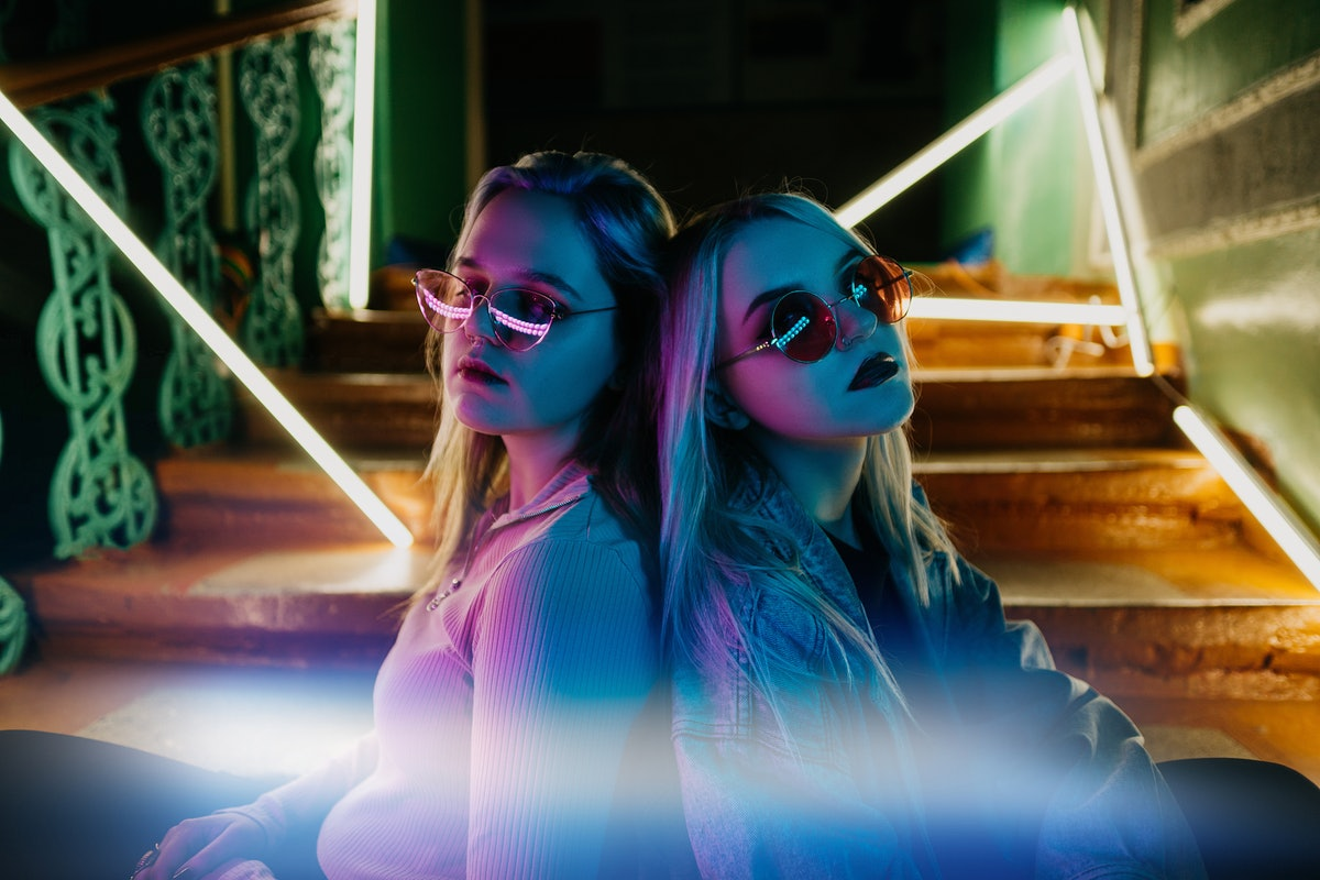 2 young woman posing back to back with sunglasses on during the full blue moon in Aquarius.