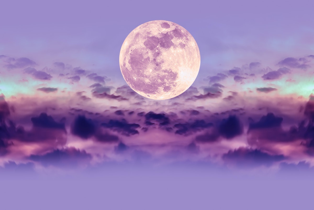 Purple nature background of night sky and silhouette of clouds with the August 2021 full blue moon i...