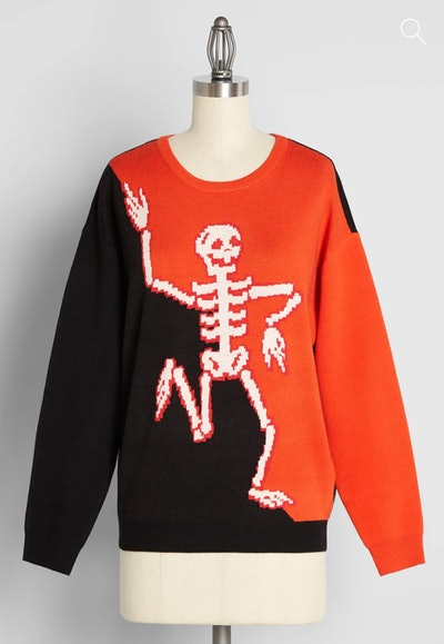 Mannequin displaying black and white sweater with dancing skeleton