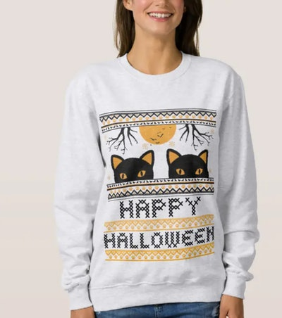Woman in grey sweater with faux knit details with black cats