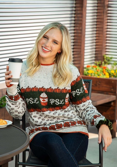 Woman sitting down, holding to-go coffee cup, wearing PSL sweater